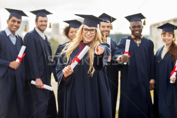 Feliz estudiante diploma senalando dedo educación Foto stock © dolgachov