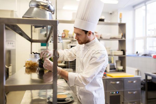 male chef cooking at restaurant kitchen Stock photo © dolgachov