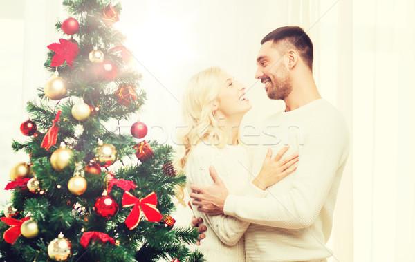 happy couple hugging near christmas tree at home Stock photo © dolgachov