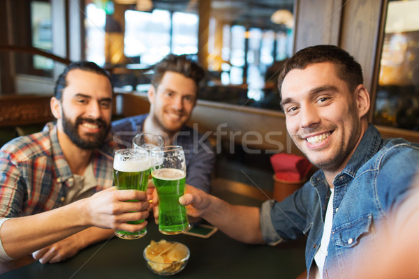 friends with green beer taking selfie at pub Stock photo © dolgachov