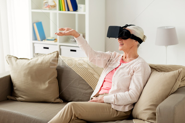 old woman in virtual reality headset or 3d glasses Stock photo © dolgachov