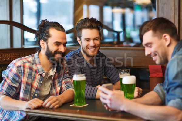 Freunde Smartphone trinken grünen Bier Veröffentlichung Stock foto © dolgachov