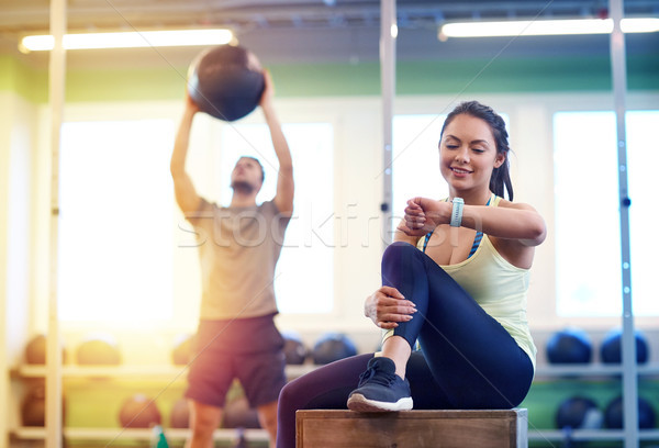 man and woman with ball and fitness tracker in gym Stock photo © dolgachov