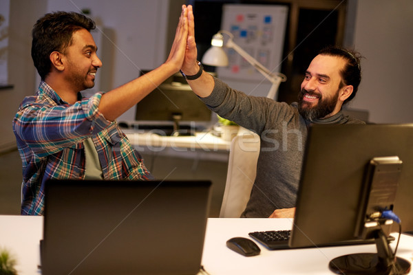 creative team making high five at night office Stock photo © dolgachov