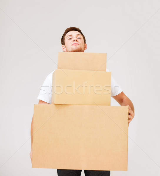 young man carrying carton boxes Stock photo © dolgachov