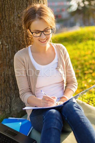 Mosolyog tinédzser szemüveg ír notebook oktatás Stock fotó © dolgachov