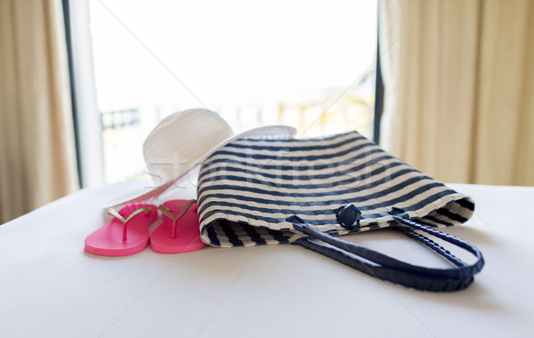 close-up of beach bag, hat and flip-flop on bed Stock photo © dolgachov