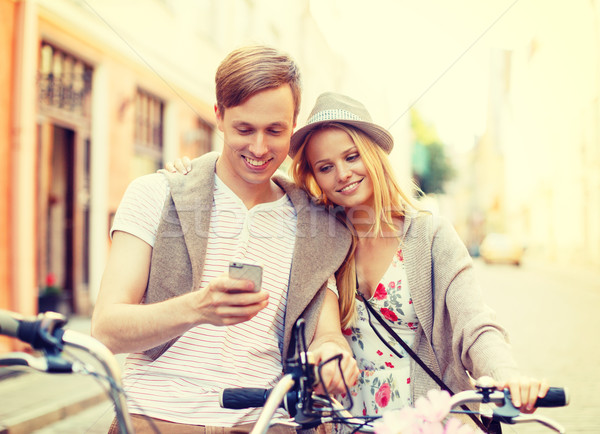 couple with smartphone and bicycles in the city Stock photo © dolgachov