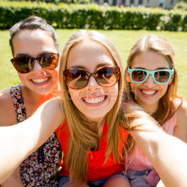group of smiling teen girls taking selfie in park Stock photo © dolgachov