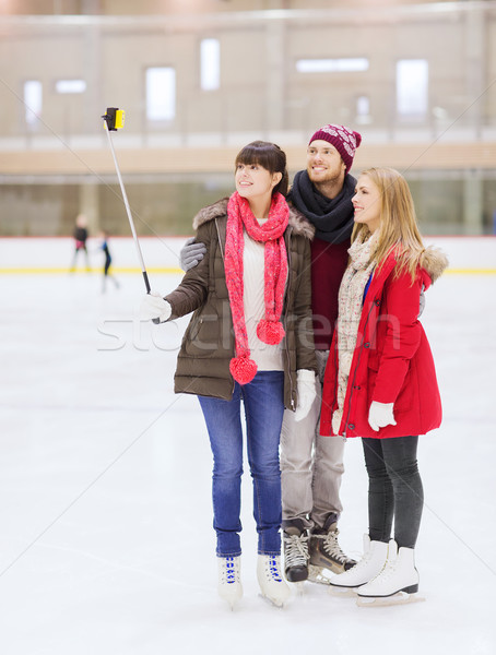 happy friends with smartphone on skating rink Stock photo © dolgachov