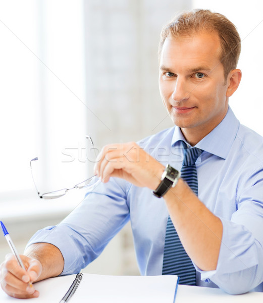 Biznesmen okulary piśmie notebooka zdjęcie przystojny Zdjęcia stock © dolgachov