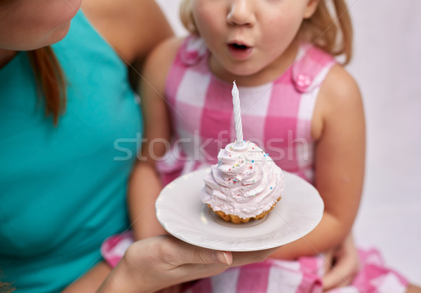 happy mother and girl blowing out cupcake candle Stock photo © dolgachov