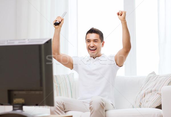 smiling man watching sports at home Stock photo © dolgachov