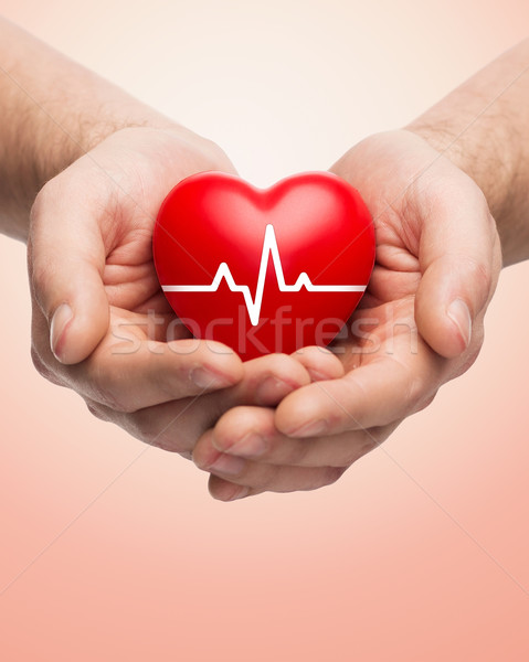 close up of hands holding heart with cardiogram Stock photo © dolgachov