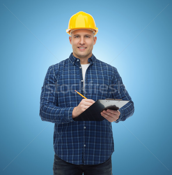 smiling male builder in helmet with clipboard Stock photo © dolgachov