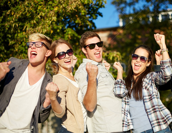 group of happy friends showing triumph gesture Stock photo © dolgachov