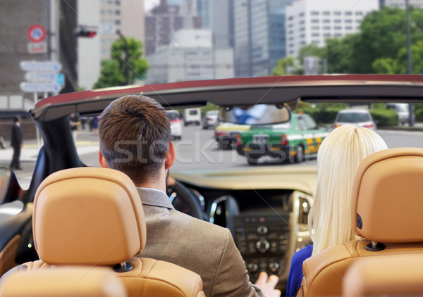 couple driving in cabriolet car over city street Stock photo © dolgachov