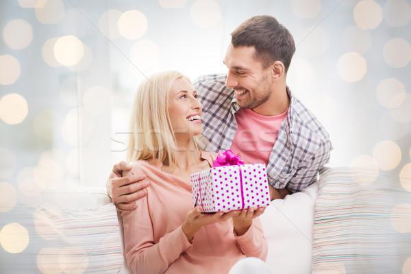 happy man giving woman present over holiday lights Stock photo © dolgachov