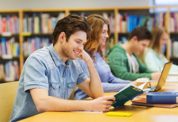 happy student boy reading books in library Stock photo © dolgachov