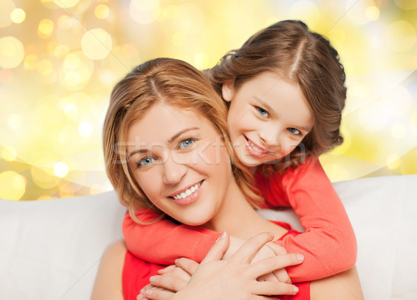 happy mother and daughter hugging over lights Stock photo © dolgachov