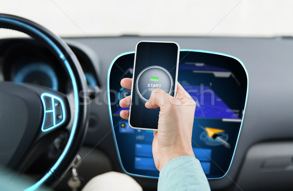 Stock photo: hands with start engine icon on smartphone in car