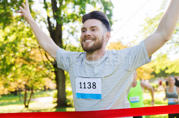 Stock photo: happy young male runner winning on race finish