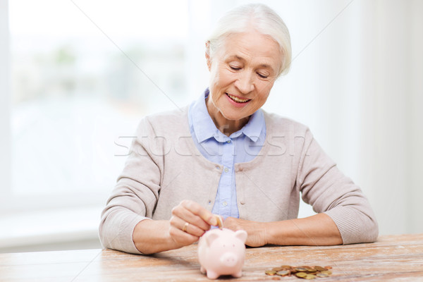 senior woman putting money to piggy bank at home Stock photo © dolgachov