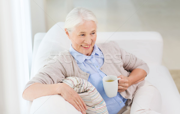 happy senior woman with cup of tea at home Stock photo © dolgachov
