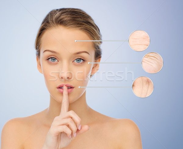 beautiful young woman holding finger on lips Stock photo © dolgachov