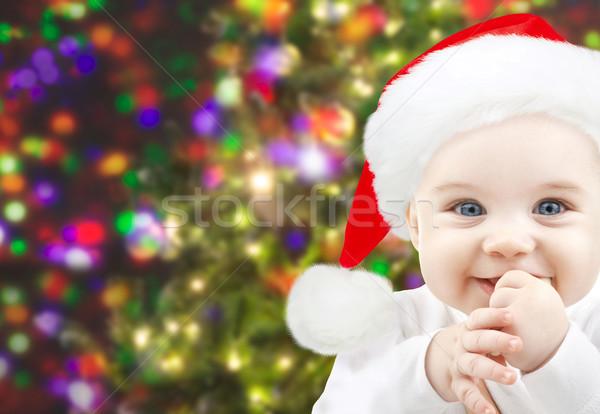 happy baby in santa hat over christmas lights Stock photo © dolgachov