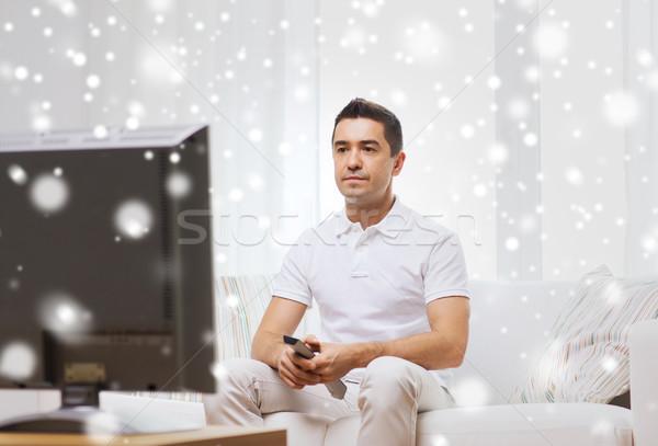 man with remote control watching tv Stock photo © dolgachov