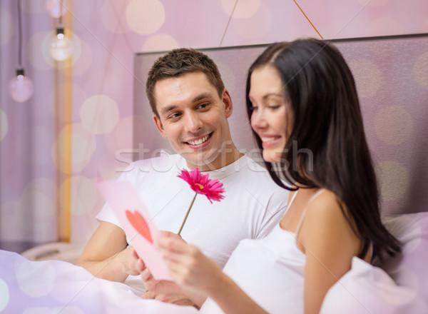 Uśmiechnięty para bed pocztówkę kwiat Zdjęcia stock © dolgachov