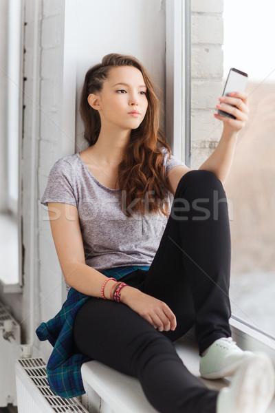 sad pretty teenage girl with smartphone texting Stock photo © dolgachov