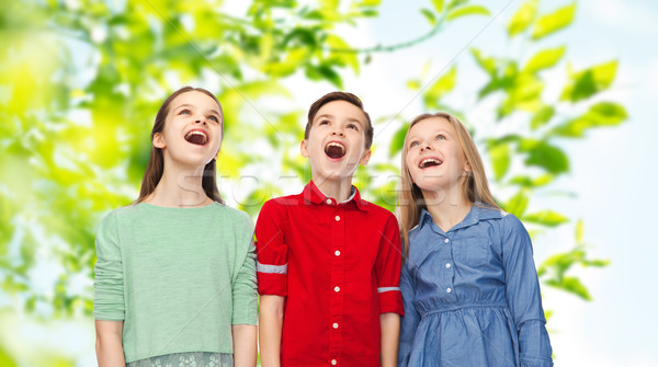 amazed boy and girls looking up Stock photo © dolgachov