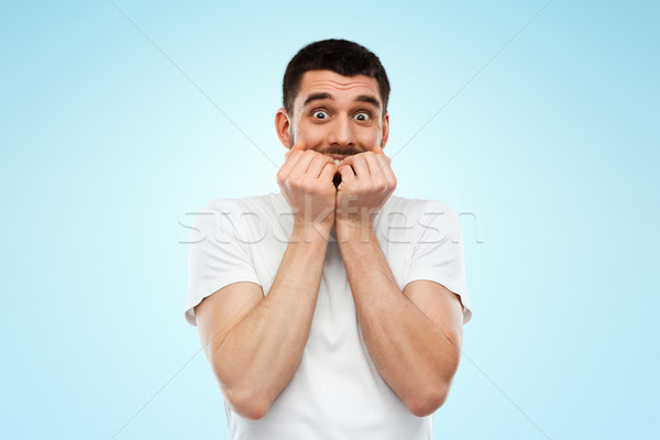 scared man in white t-shirt over blue background Stock photo © dolgachov