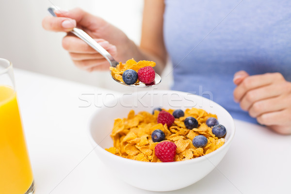 close up of woman eating corn flakes for breakfast Stock photo © dolgachov