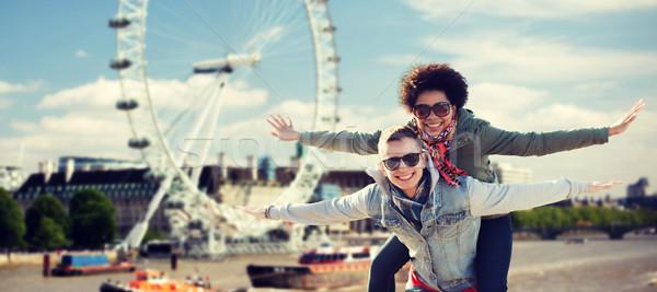 happy teenage couple having fun over london Stock photo © dolgachov