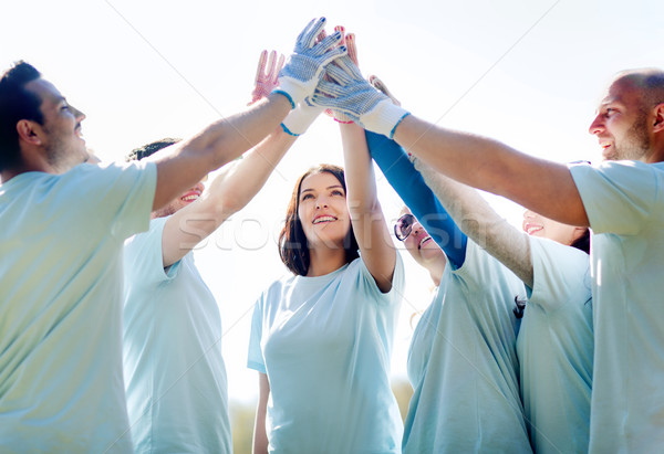 group of happy volunteers making high five in park Stock photo © dolgachov