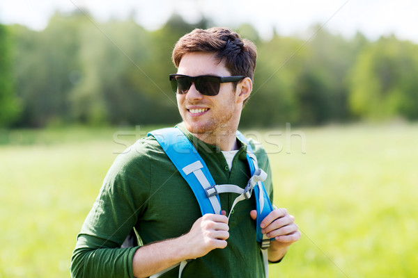 happy young man with backpack hiking outdoors Stock photo © dolgachov