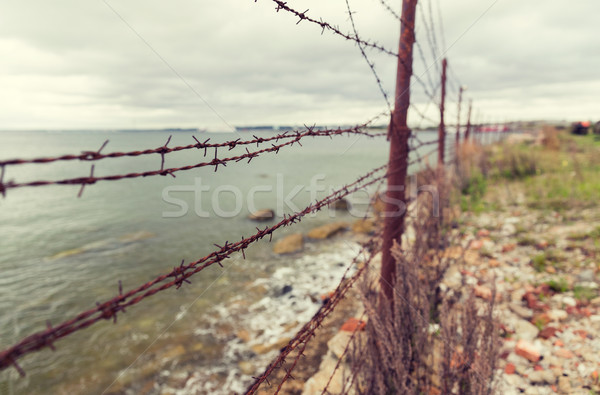 Stock photo: barb wire fence over gray sky and sea