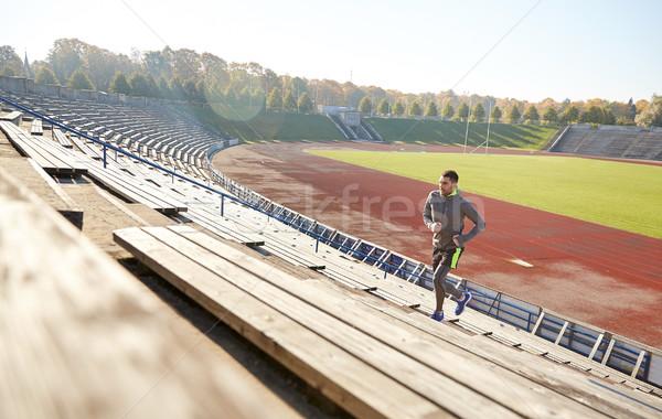 Feliz moço corrida em cima estádio fitness Foto stock © dolgachov