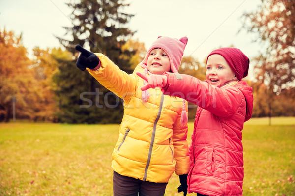 happy little girls pointing finger in autumn park Stock photo © dolgachov