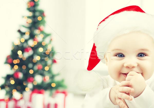 happy baby in santa hat over christmas tree lights Stock photo © dolgachov