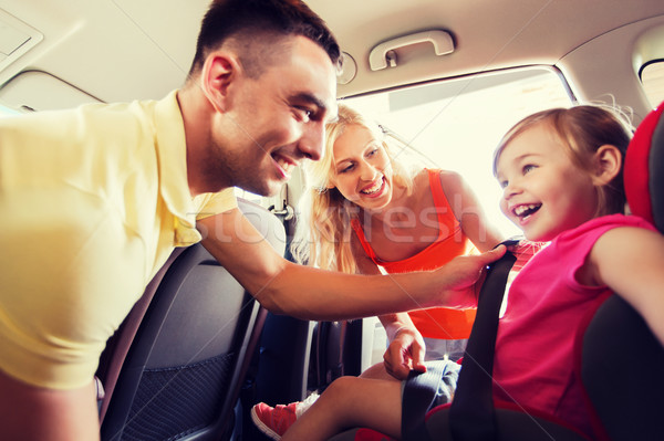 happy parents fastening child with car seat belt Stock photo © dolgachov
