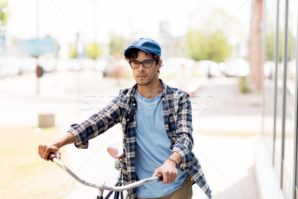 young man with fixed gear bicycle walking in city Stock photo © dolgachov