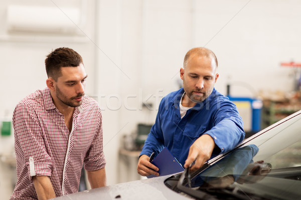 Stock photo: auto mechanic with clipboard and man at car shop