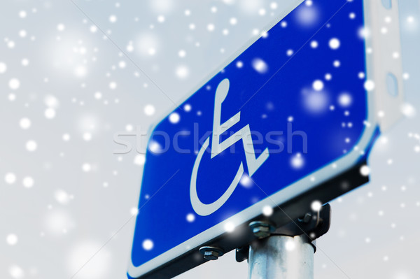 close up of road sign for disabled over snow Stock photo © dolgachov
