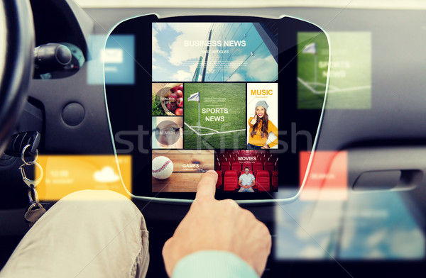 Stock photo: close up of male hand media applications in car