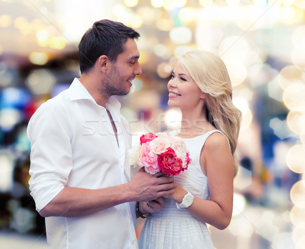 happy couple with flowers over lights background Stock photo © dolgachov