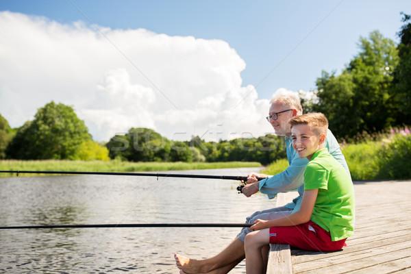 grandfather and grandson fishing on river berth Stock photo © dolgachov